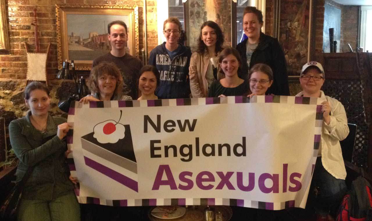 [A picture of some of the New England Aces standing behind our Pride banner]